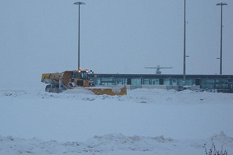 Engin en action sous la neige sur piste d'aéroport