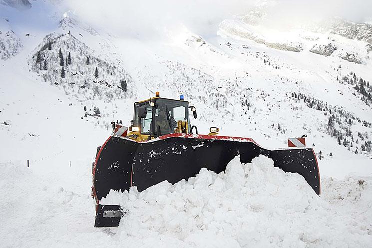 Engin équipé d'une lame tri-axiale en action dans la neige